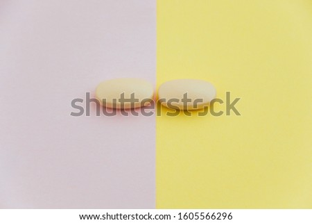 Two identical pills separated on different backgrounds, separation concept #1605566296
