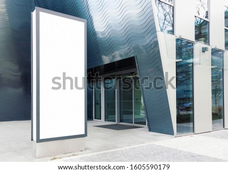 Blank standing outdoor billboard with white copy space to add multiple company names and logos with modern office building in background