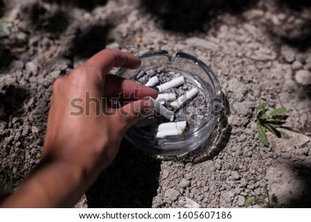 Unrecognizable person  extinguishes cigarette in ashtray.Horizontal composition,outdoor shot. There are many cigarettes in the ashtray #1605607186