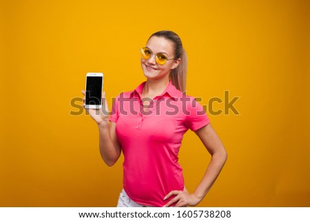 Bright and cheerful young woman in a pink t-shirt on a yellow background. Girl uses smartphone for communication and useful applications #1605738208