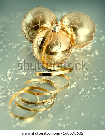 golden shiny christmas balls with snow decoration over silver background. selective focus. retro toned blurred effect #160578632