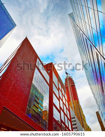 Bottom up Street view on Financial District of Lower Manhattan, New York City, NYC, USA. Skyscrapers tall glass buildings United States of America. Blue sky on background. Mixed media. #1605790615