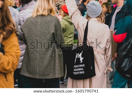 "People protesting on the street against animal abuse. Woman holds black fabric bag with phrase "" Fighting animal testing "". Save animals. Cruelty free. Freedom. Animal rights protest. Rally. March #1605790741"
