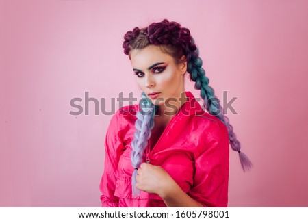 Beautiful stylish girl with colorful kanekalon braided in her hair. Pretty woman with colorful violet ombre hair and pro makeup isolated at pink background. Hairdresser salon concept #1605798001