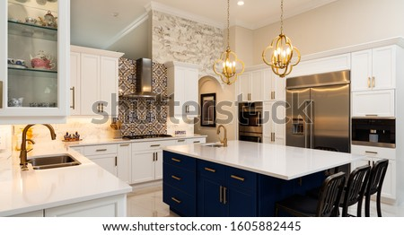 Beautiful luxury home kitchen with white cabinets. Royalty-Free Stock Photo #1605882445