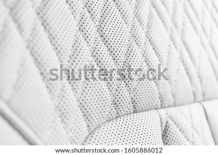 Modern luxury Car white leather interior. Part of perforated leather car seat details. White Perforated leather texture background. Texture, artificial leather with stitching. Perforated seats #1605886012