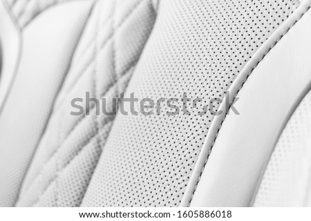 Modern luxury Car white leather interior. Part of perforated leather car seat details. White Perforated leather texture background. Texture, artificial leather with stitching. Perforated seats #1605886018