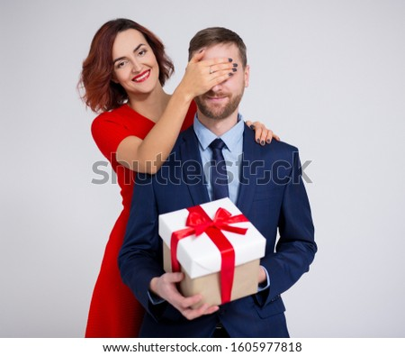 Valentine's day, christmas or surprise concept - woman surprising her boyfriend with gift over white background #1605977818