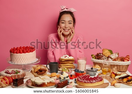 People, sweet tooth and temptation concept. Pleased Korean woman wears headband, knitted jumper, has good appetite to eat desserts, isolated over pink background, tries to loose weight but cheats #1606001845