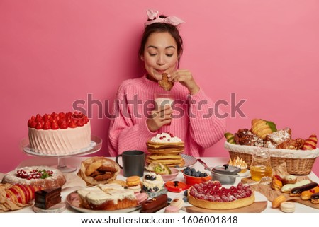 Hungry lovely Korean girl eats cookies and drinks fresh milk, enjoys sweet lunch, sits at big table with various desserts, dressed in oversized jumper, isolated over rosy wall. Tasty sweet snack #1606001848