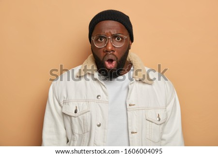 Shocked emotional bug eyed man stares at camera with omg expression, expresses astonishment and great wonder, wears big spectacles, white clothes, isolated over beige background. Reaction, emotions #1606004095