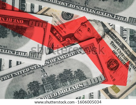 The bright red arrow icon on a background of money. The concept of changing course of US dollar on the market. Devaluation, collapse, stagnation of the economy. #1606005034