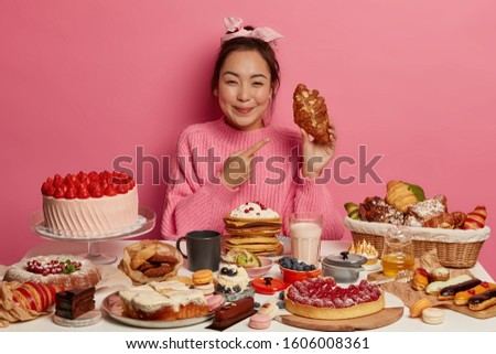 Beautiful smiling Asian woman points at delicious croissant, wears knitted sweater, sits at festive table with tasty sweet desserts, drinks fresh milk, cannot imagine her life without sugar. #1606008361