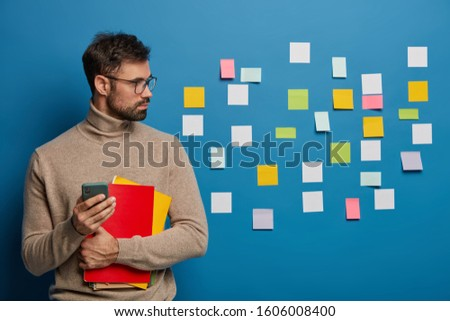 Isolated shot of serious male student with thick beard uses mobile phone, looks aside, stands against blue wall, sticky notes, searches creative ideas for project, dressed casually. Studying concept #1606008400