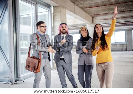 Two arab foreign investors standing in building in construction process and listening to real estate agent who is trying to convince them to buy it. #1606017517
