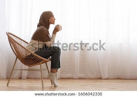 Morning Relax. Young Muslim Woman In Hijab Sitting In Wicker Chair, Drinking Coffee Or Tea Against Window At Home, Free Space #1606042330