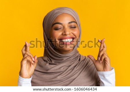 Please, please, please. Closeup portrait of dreamy black muslim girl in hijab crossing fingers, making wish, over yellow background #1606046434