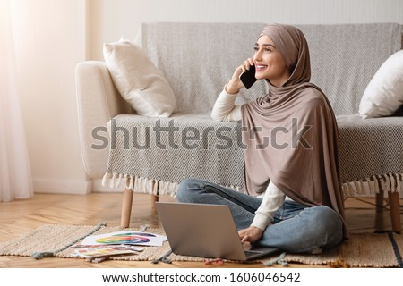 Work Opportunities For Muslim Women Concept. Smiling Arabic Girl In Hijab Talking On Cellphone And Using Laptop While Sitting On Floor At Home. Royalty-Free Stock Photo #1606046542
