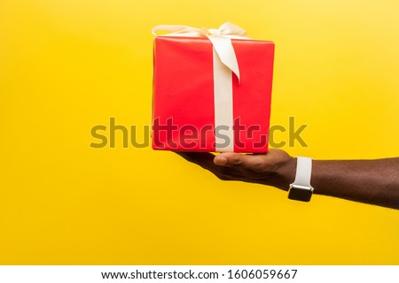 Closeup side view of male hand with wristwatches holding out red gift box with ribbon, giving present on holiday, bonuses and surprises concept. indoor studio shot isolated on yellow background #1606059667