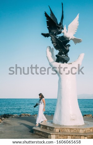 Kusadasi, Aydin Province, Turkey. Young Woman Tourist Traveler Photographer Taking Pictures Photos Near Hand Of Peace Monument On Waterfront In Sunny Summer Day. Sculpture At Aegean Coast, Turkey.
