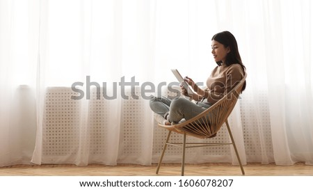 Lazy weekend. Girl using tablet, sitting in wicker chair against window, panorama with empty space #1606078207