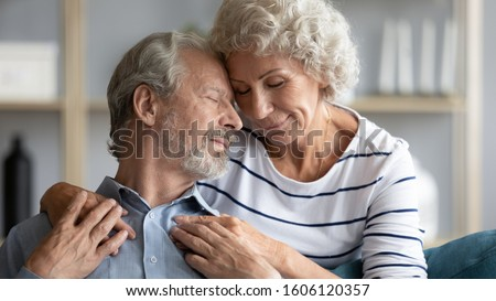 Hoary wife hugs from behind snuggle to beloved husband 60s loving couple closed eyes enjoy tender moment, showing care, promising to love each other until the end of life in sorrow and in joy concept