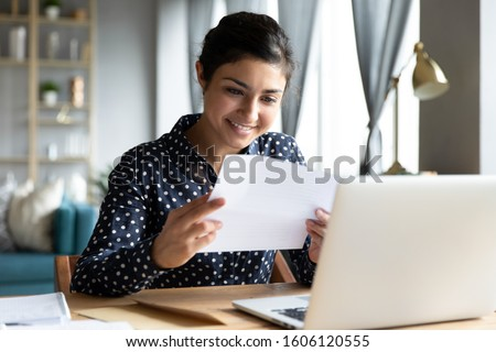 Smiling young indian woman holding paper bill letter doing paperwork bill reading good news check post mail sit at home table, happy lady customer receive bank receipt sheet tax refund notification Royalty-Free Stock Photo #1606120555