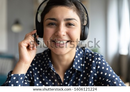 Smiling indian girl teacher counselor telesales agent wear wireless headset look at camera webcam, distance teaching, customer support service concept, telemarketing professional closeup portrait #1606121224