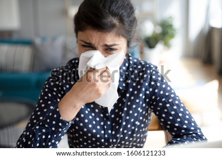 Ill upset indian girl holding paper tissue blowing running nose sneezing in handkerchief got flu fever caught cold influenza sit at home, flue sinus virus disease symptom concept, face close up view #1606121233