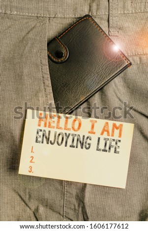 Writing note showing Hello I Am Enjoying Life. Business photo showcasing Happy relaxed lifestyle Enjoy simple things Small wallet inside trouser front pocket near notation paper. #1606177612