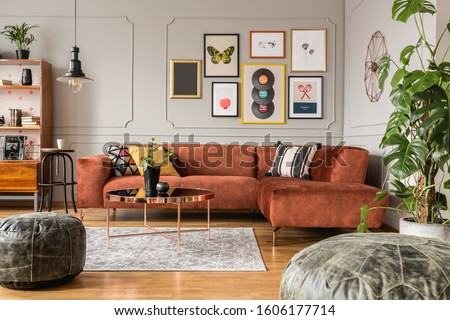 Gallery of trendy posters in elegant grey living room interior with brown corner sofa Royalty-Free Stock Photo #1606177714