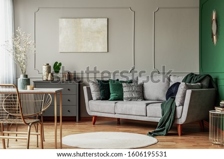 Stylish emerald green and grey living room interior design with abstract painting on the wall Royalty-Free Stock Photo #1606195531