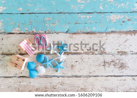 Summer time vacation concept. Beach Accessories model wooden house,chair,shoe with sea shells and starfish on Blue vintage wooden background with copy space. flat lay picture