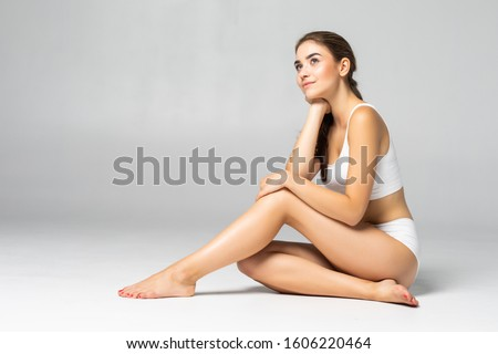 Young woman in cotton underwear sitting on white background #1606220464