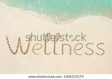Wellness concept photo. Word Wellness handwritten on the sand. Beach and soft wave background. Royalty-Free Stock Photo #1606233574