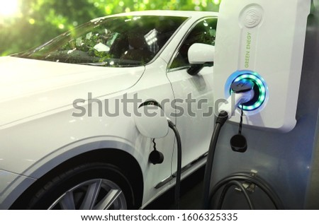 Power supply connect to electric vehicle or EV car for charge to the battery. Charging technology industry transport in Eco-friendly alternative energy concept to green energy. #1606325335