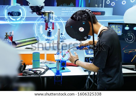 Virtual reality and neural network technology in industry. Man wearing VR glasses connect to neural network for working with Robotic arm, programing, control, sharing and working together. #1606325338