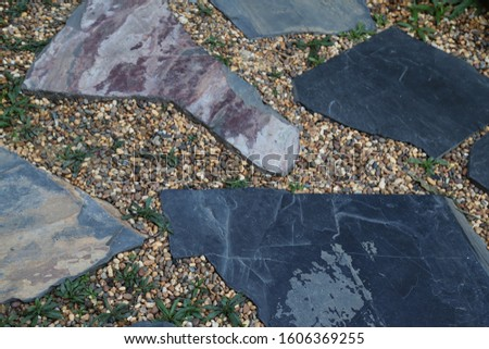 Closeup of classical designed stones and pebbles ground of walkway in the garden. #1606369255
