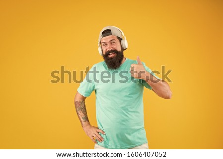 Thumbs up to hipster music. Brutal hipster listening to music on yellow background. Hipster with beard and mustache wearing modern headphones. Bearded man in trendy hipster style. #1606407052