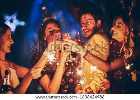Group of friends having fun and holding sparklers at New Year's party #1606424986