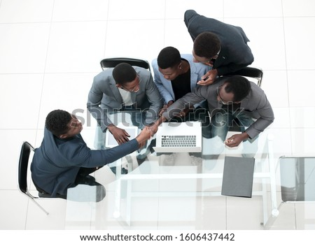 top view. business colleagues shaking hands during office meeting. #1606437442