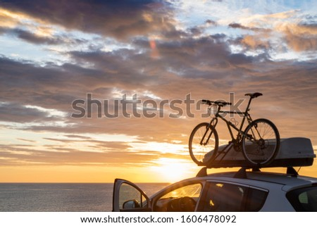 Mounted mountain bicycle silhouette on the car roof with evening sun light rays background. Safe sport items transportation using a car concept image. Royalty-Free Stock Photo #1606478092
