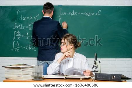 Teaching in university. University education. Knowledge transfer. Teacher and student near chalkboard. College university education. High school. Solving task. Man writing on chalkboard math formulas. #1606480588