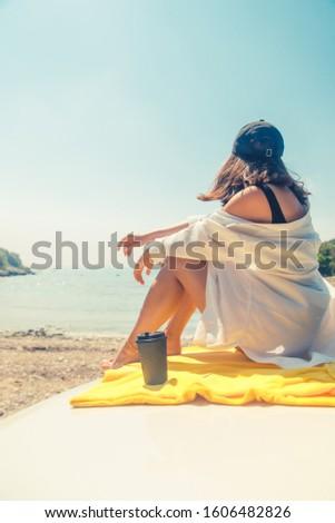 woman sitting at car hood drinking coffee enjoying view of the sea