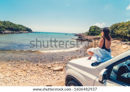 woman laying at car hood with view of sea summer beach