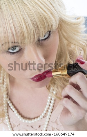 Sexy Confident Sensual Young Blonde Woman Applying Red Lipstick Make Up Or Cosmetics, Getting Ready To Go Out #160649174