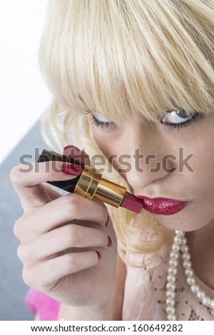 Sexy Confident Sensual Young Blonde Woman Applying Red Lipstick Make Up Or Cosmetics, Getting Ready To Go Out #160649282