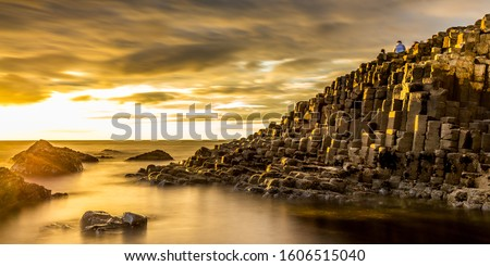 View of the Giant's Causeway in Northern Ireland at sunset with a golden light and dramatic sky Royalty-Free Stock Photo #1606515040