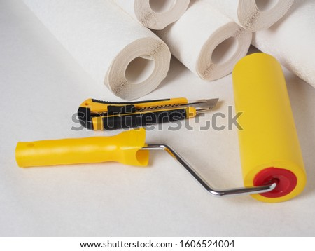 wallpaper rolls, a construction knife for wallpaper and a roller on a white background, tools for repairing the house, wallpapering the walls #1606524004