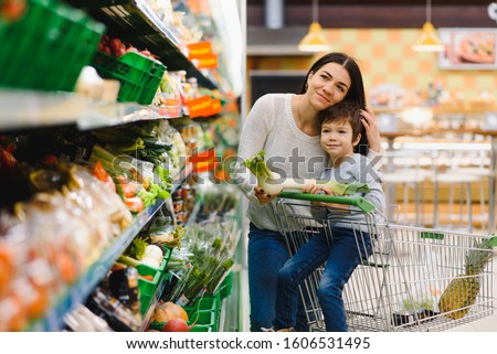 Mother and child shopping at farmer's market for fruits and vegetables #1606531495